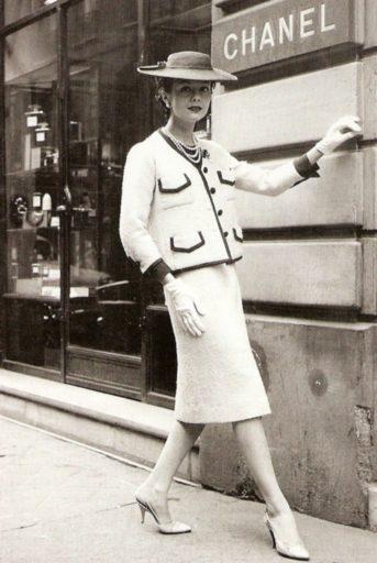 Modelo posa em frente à Maison Chanel, usando o famoso tailleur