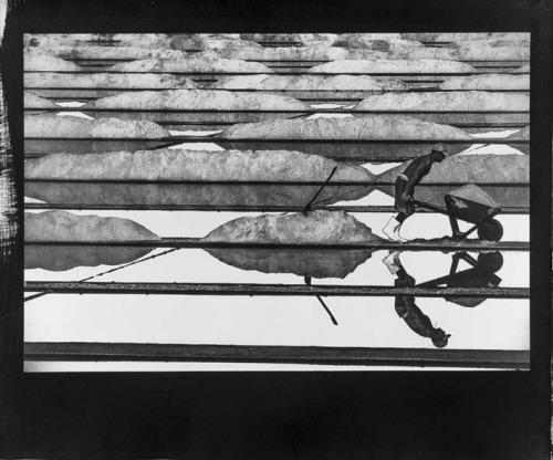 Foto em preto e branco mostrando uma salina de onde se extrai o sal.